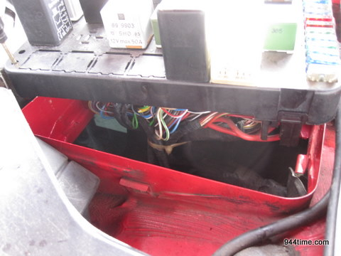 the 1986 944) is by first removing the fuse panel (unscrew two  thumbscrews in corner and wiggle it out) and then removing a plastic shield  right below